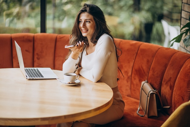カフェでコンピューターに取り組んでいる若い美しいビジネス女性