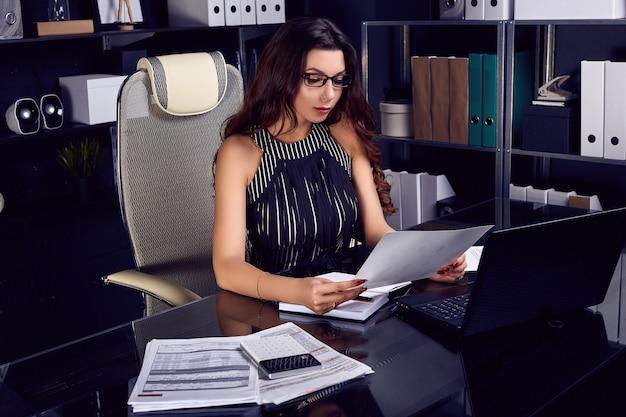 Young beautiful business woman working at stylish black desk