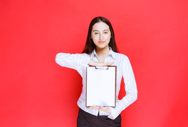 赤い壁に空のクリップボードを保持している若い美しい実業家。