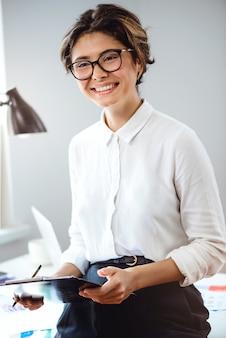 フォルダーを保持している若い美しい実業家、オフィスの職場で笑っています。