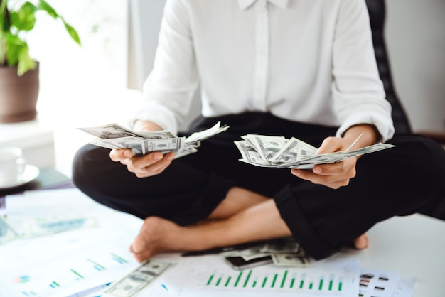 Young beautiful businesswoman holding money, sitting on table at workplace.
