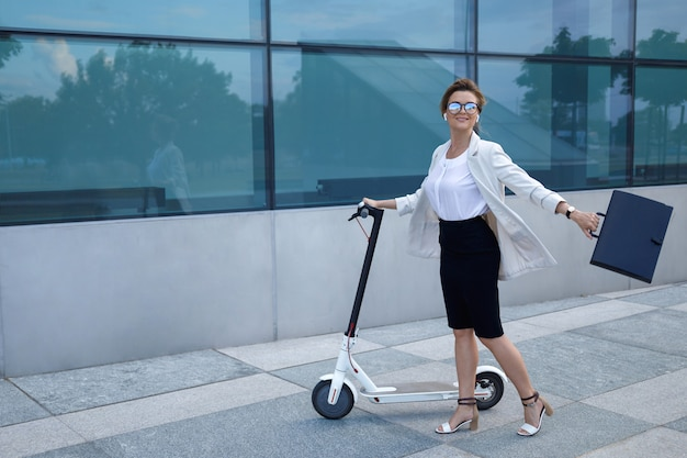 Young and beautiful businesswoman rides electric scooter in the city