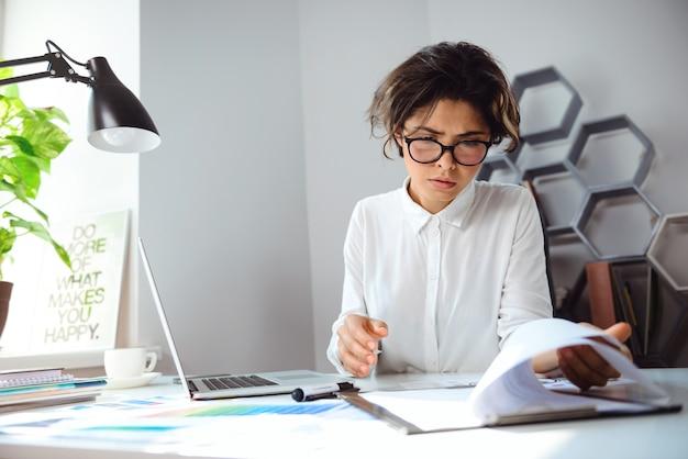 オフィスの職場で座っている若い美しい女性実業家。