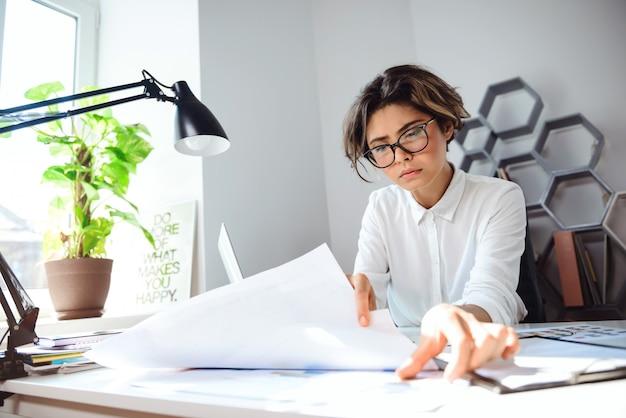Giovane imprenditrice bella seduta sul posto di lavoro in ufficio.