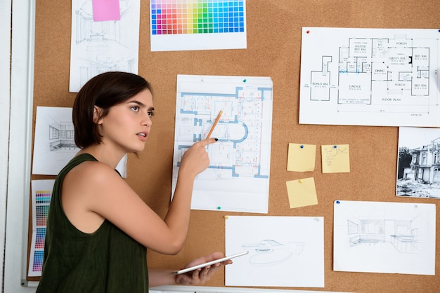 Young beautiful businesswoman standing near desk with drawings