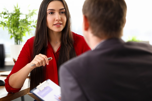 Young beautiful businesswoman in stylish official clothes sitting in office and talking with man colleague. business people, negotiations, people working in office concept
