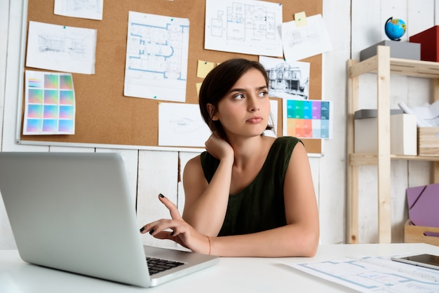 Young beautiful businesswoman thinking, sitting at workplace with laptop