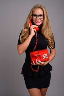 Young beautiful businesswoman with blond hair against gray backg