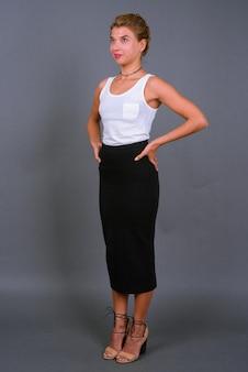 Молодая красивая деловая женщина со светлыми волосами на сером