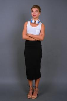 Молодая красивая деловая женщина со светлыми волосами в наушниках на сером