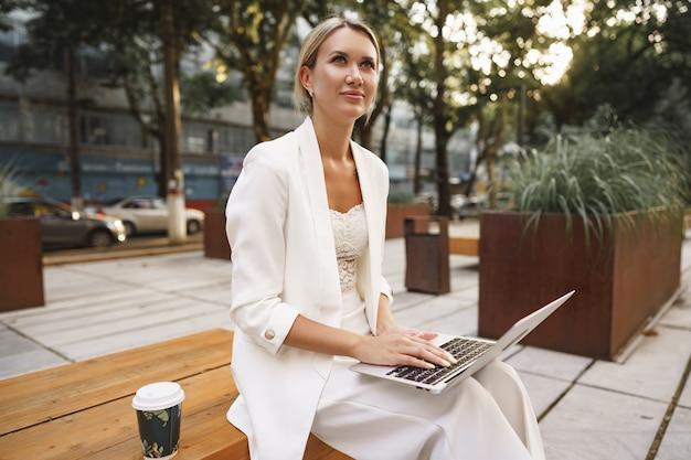 Молодая красивая деловая женщина работает на ноутбуке, сидя на скамейке на улице
