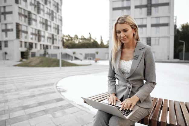 거리의 벤치에 앉아 노트북 작업을 하는 젊은 아름다운 사업가