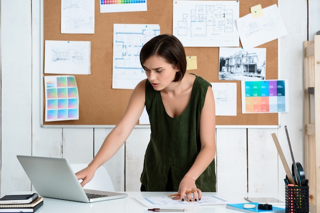 Young beautiful businesswoman working with drawings at workplace