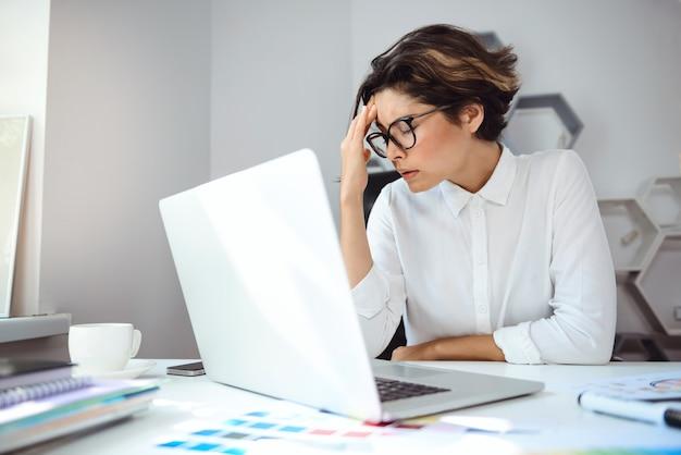 Молодая красивая коммерсантка работая с компьтер-книжкой на рабочем месте в офисе.