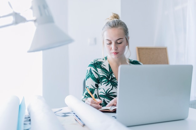Young beautiful businesswoman writing diary in office
