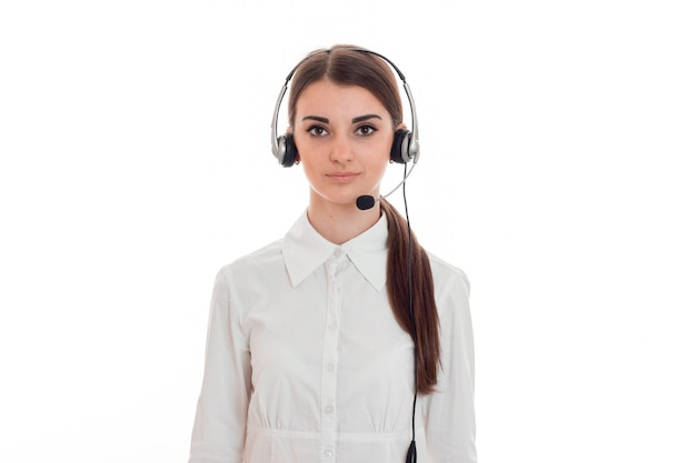 Young beautiful call center operator in white shirt with headphones isolated on wall in studio