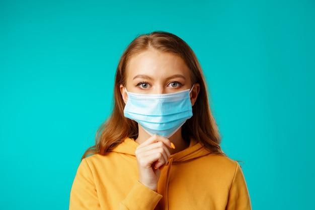 Молодая красивая повседневная женщина в защитной медицинской маске на синем фоне Premium Фотографии