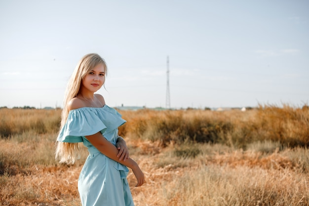 Young beautiful caucasian blonde girl in light blue dress stands on the field with the sun-scorched grass