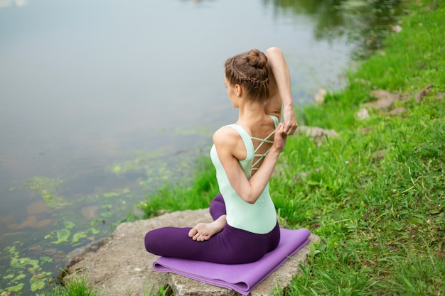 Young beautiful caucasian brunette girl doing yoga on a green lawn against the background of the river