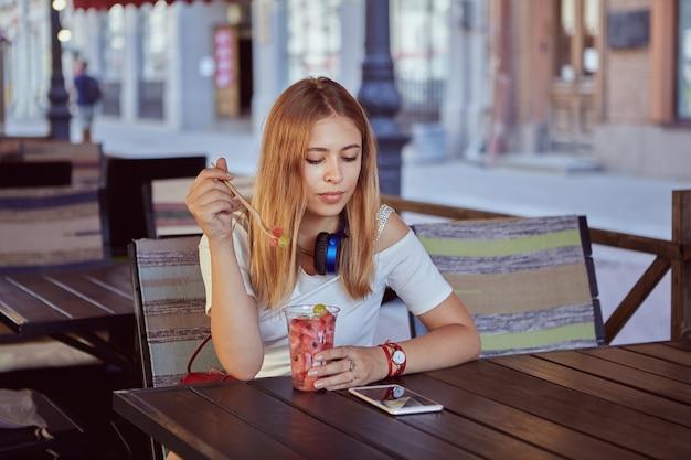 금발 머리를 가진 약 25 세 젊은 아름 다운 백인 여성은 야외에 앉아 휴대 전화의 화면을 보면서 과일 디저트를 먹고 있습니다.