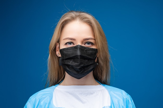 Young beautiful caucasian female in blue medical gown and with white medical mask on her face looks on the camera