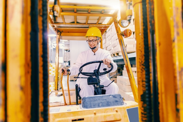 Young beautiful caucasian female woman in white uniform and with protective helmet on head driving forklift in warehouse.