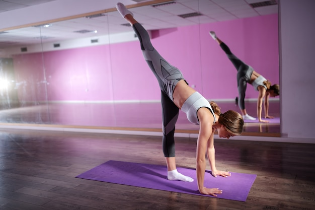 Young beautiful caucasian fit brunette stretching leg while leaning on mat.