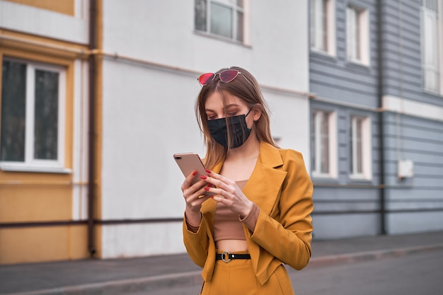 Young beautiful caucasian girl 20 years wear black face mask protection against epidemic coronavirus covid-19 walks down the street looks at the phone screen.