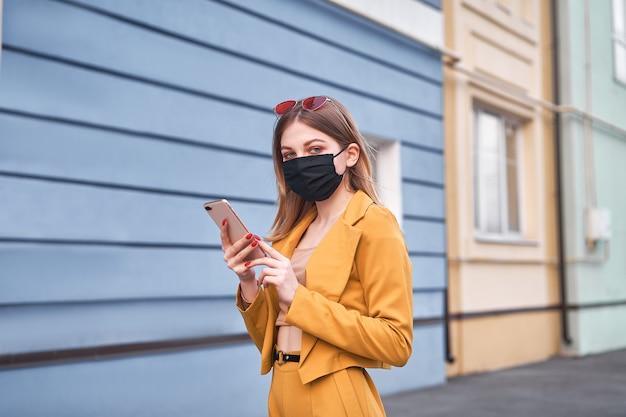 Молодая красивая кавказская девушка 20 лет носит черную маску защиты от эпидемического коронавируса ковид-19 ходит по улице, смотрит на экран телефона.