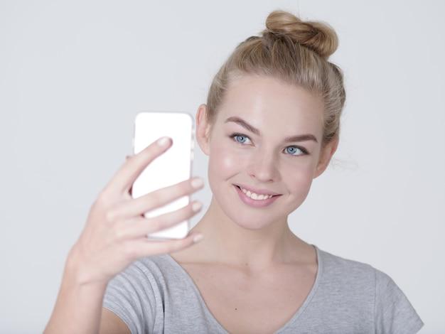 젊은 아름 다운 백인 여자는 selfies. 손에 모바일 휴대 전화와 함께 행복 한 멋진 여자