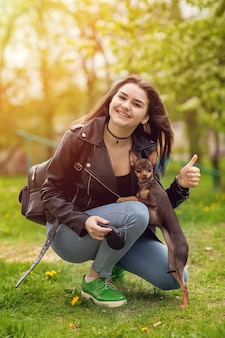 Young beautiful caucasian girl playing with dog russian toy terrier outdoors