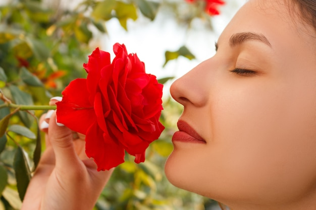 Young beautiful caucasian girl smelling red roses in the garden on sunny day
