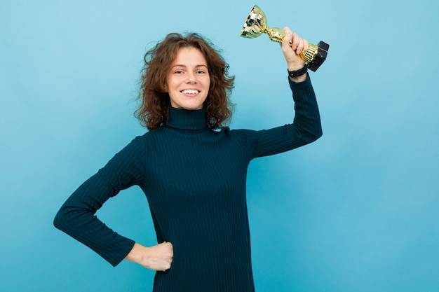 Young and beautiful caucasian girl with curly hair keeps golden goblet and smiles, portrait isolated on blue background