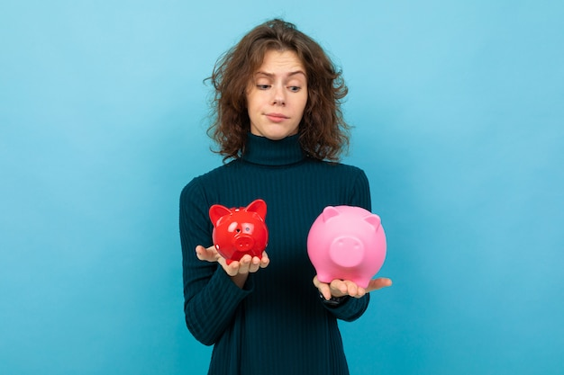 Young and beautiful caucasian girl with curly hair keeps small red pig moneybox, big pink pig moneybox and smiles, portrait isolated on blue background