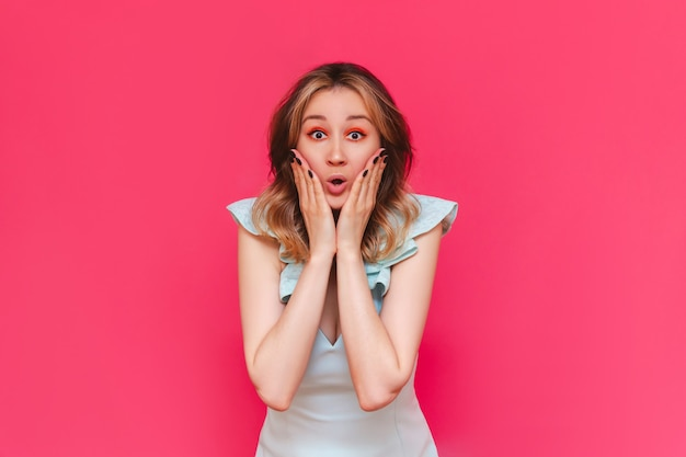 A young beautiful caucasian impressed brownhaired woman with bright make up in a stylish light blue dress surprised by the news about a sale and discounts  isolated on a bright color pink wall