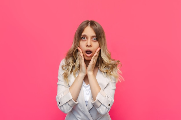 A young beautiful caucasian impressed surprised shocked blonde woman with wavy hair in a stylish clothing surprised by the news about a sale and discounts isolated on a bright color pink wall
