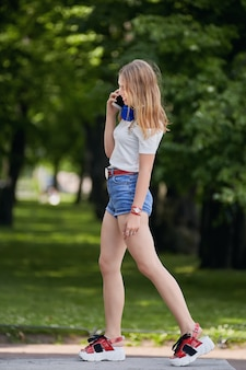 Young beautiful caucasian lady about 25 years old in shorts and platform shoes.