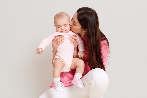 生まれたばかりの幼児の赤ちゃんのドレスのボディースーツと靴下でポーズをとる長い黒髪の若い美しい白人の母親。白い壁に隔離されたカジュアルな服を着ている女性。