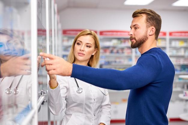 젊은 아름 다운 백인 약사는 현대 약국에서 고객과 함께 노력하고 있습니다