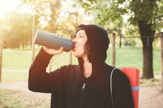 Young beautiful caucasian sportive woman outdoor drinking from reusable stainless bottle