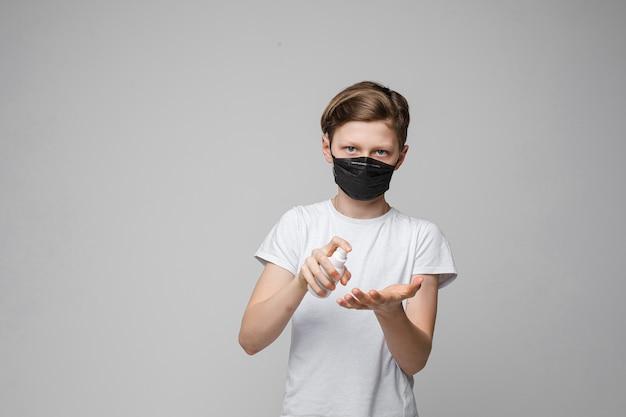 Il giovane bello adolescente caucasico in maglietta bianca, jeans neri sta con la mascherina medica nera disinfetta le sue mani con l'anticettico