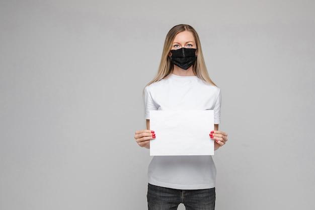 Il giovane bello adolescente caucasico in maglietta bianca, jeans sta con la mascherina medica nera tiene il broadsheet bianco
