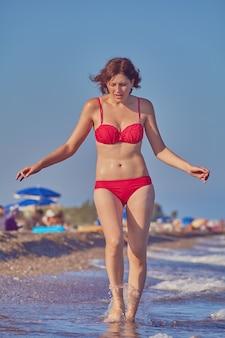 Молодая красивая кавказская женщина около 19 лет в красном купальнике гуляет по пляжу во время морского сезона летом