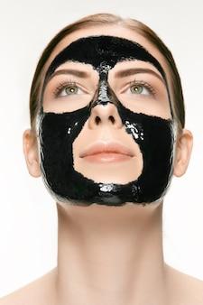 치료용 검은 진흙의 얼굴에 검은 화장용 마스크를 바르는 젊은 백인 여성. 스파 트리트먼트와 얼굴 미용 개념입니다. 여성의 얼굴 관리와 완벽한 피부 개념