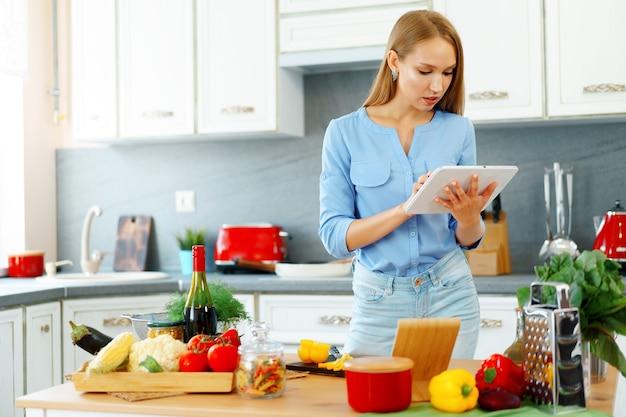 Молодая красивая кавказская женщина готовит и использует свой цифровой планшет на кухне дома