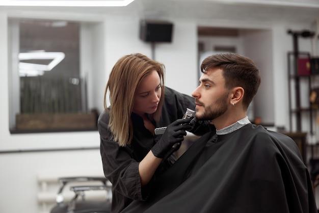 Молодая красивая кавказская женщина-парикмахер стригет бороду красивому мужчине в современной парикмахерской