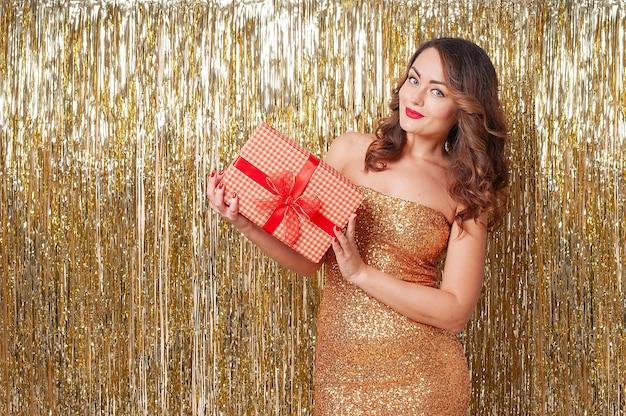Молодая красивая кавказская женщина в золотом платье держит красную подарочную коробку, развлекаясь на вечеринке на блестящем золотом фоне