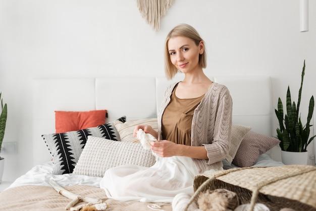 젊은 아름 다운 백인 여자는 그녀의 손에 마크라메를 들고 침대에 앉아있다