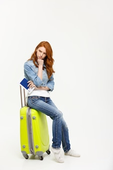 Young beautiful caucasian woman is sitting on suitecase and waiting for her flight.