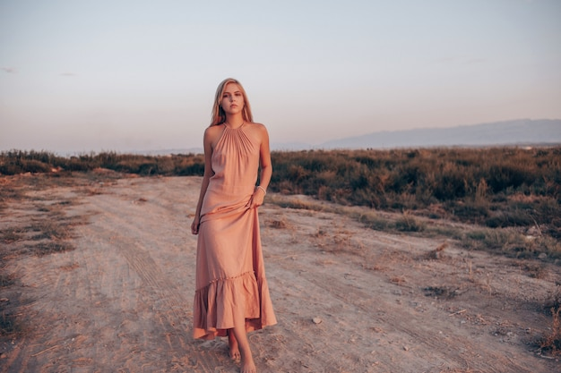 Young beautiful caucasian woman in pink dress walks on sand with bare feet during sunset